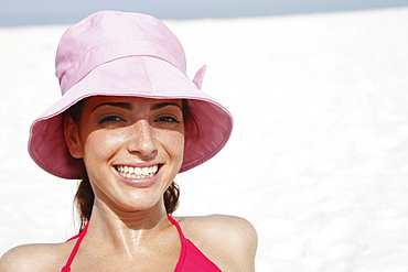 Young woman in hat sunbathing on beach