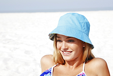 Teenage girl in hat sunbathing on beach