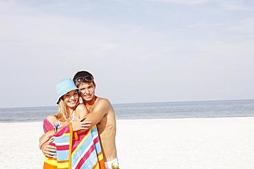 Teenage couple hugging on beach