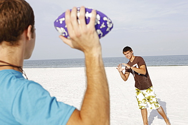 Friend playing football on beach