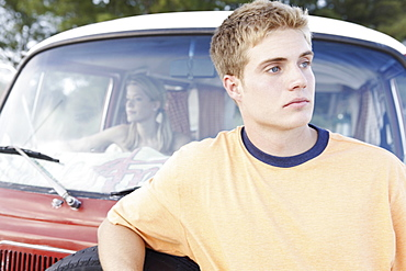 Young man leaning on van