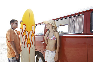 Young couple standing with surfboard by van on beach