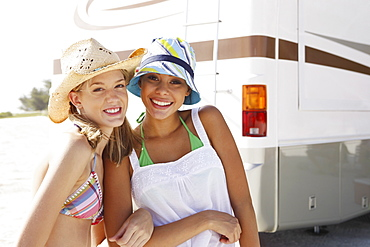 Friends posing near motor home on beach