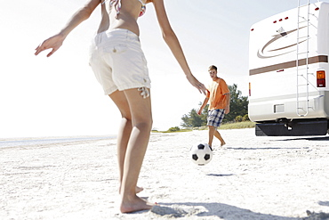 Young couple playing soccer on beach
