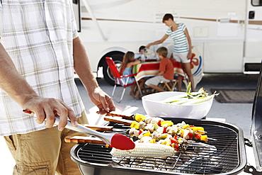 Man grilling dinner for family on beach