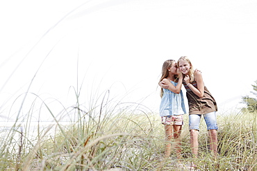 Girls telling secrets on grassy sand dune