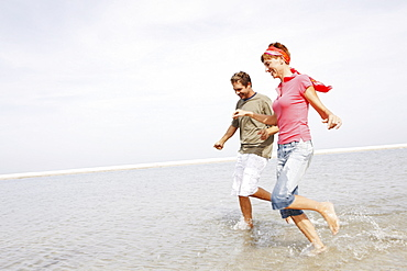 Couple running in ocean