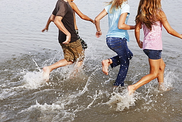 Children running in ocean