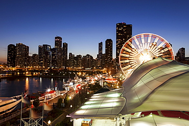Illuminated ferris wheel with skyscrapers in background, Chicago, Illinois