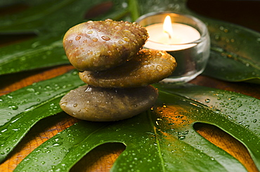 Spa stones and candle on tropical leaf, studio shot
