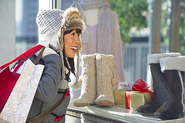 Smiling woman looking at shop display during Christmas shopping