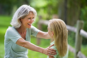 Girl (10-11) and grandmother laughing togetherness