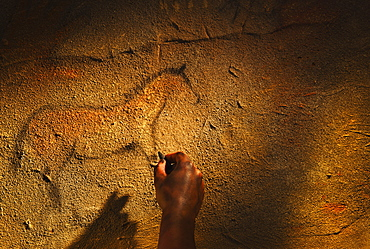Studio shot of hand making cave painting of horse