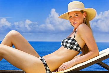 Woman sunbathing by sea
