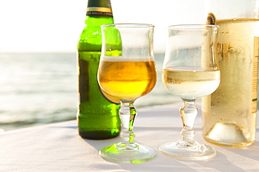 Greece, Cyclades Islands, Mykonos, Beer and wine on table by sea