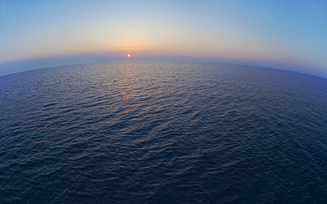 Aerial view of horizon over sea at sunrise
