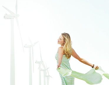 Young woman standing near wind turbines
