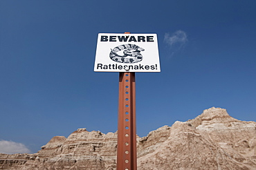 USA, South Dakota, Badlands National Park, Rattlesnake warning sign against sky, mountain in background