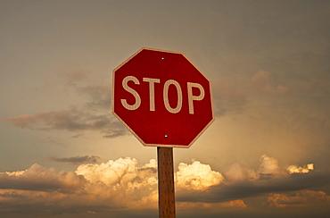 USA, South Dakota, Badlands National Park, Stop sign against sky at sunset