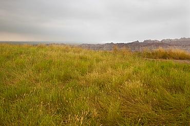 USA, South Dakota, Stormy clouds over prairie grass in Badlands National Park