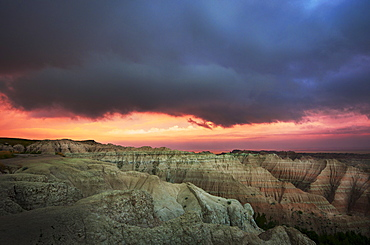 USA, South Dakota, Thick gray clouds over mountains in Badlands National Park at sunset