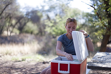 Smiling woman opening cooler in park, Davis Mountains State Park, Texas, USA