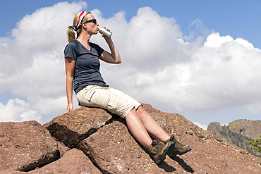 Woman sitting on rock and drinking from bottle, Big Bend National Park, Texas, USA