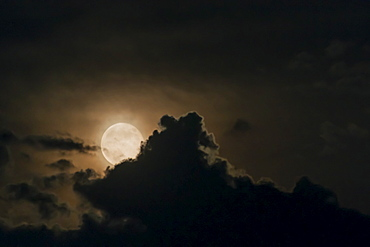 Full moon emerging from clouds