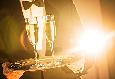 Waiter holding tray with champagne