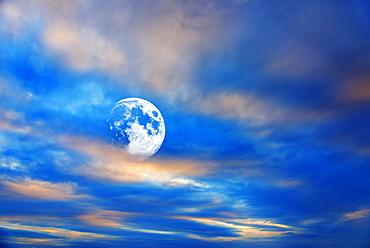 Moon behind clouds at dusk
