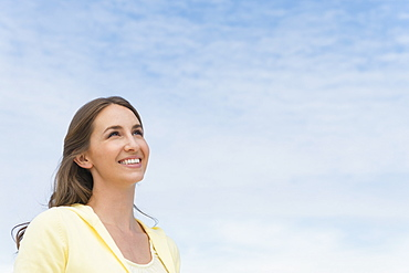 Portrait of beautiful young woman against sky
