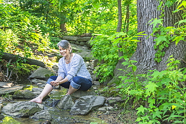 Senior woman sitting by stream, Central Park, New York City