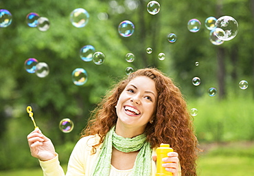 Young woman blowing bubbles in park