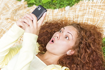 Woman lying on grass in park and using mobile phone