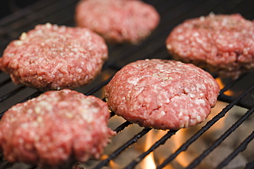 Hamburger patties cooking on grill