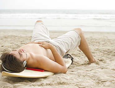 Man laying on surfboard at beach