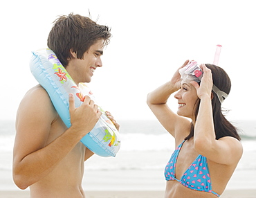 Couple smiling at each other at beach