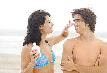 Woman putting sunscreen on man's nose at beach