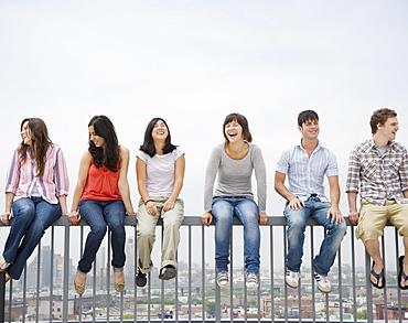Friends sitting on railing