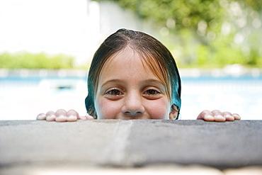 Girl peeking over edge of swimming pool