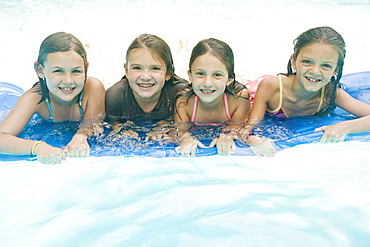 Girls resting on inflatable raft in swimming pool