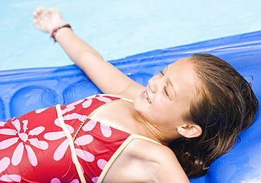 Girl playing on inflatable raft in swimming pool