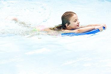 Girl using kickboard in swimming pool