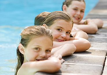 Girls in a row leaning on edge of swimming pool