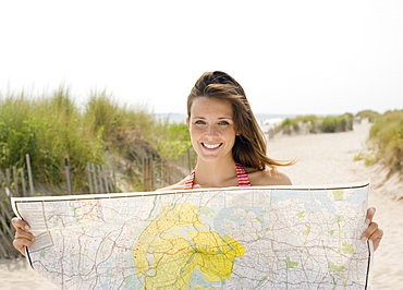 Woman holding map at beach