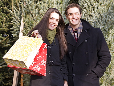 Couple with shopping bags in front of Christmas trees