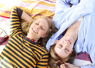 Two young women laying on blanket