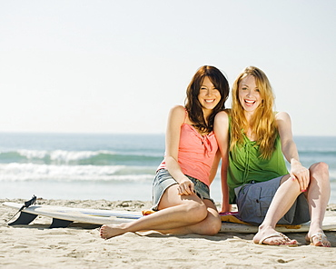 Multi-ethnic women sitting on surf board