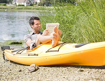 Man reading newspaper in kayak