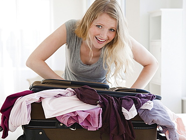young woman trying to close luggage